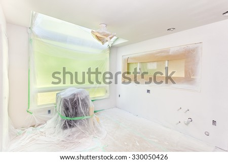 Kitchen remodel: painter's plastic covers everything not to be sprayed with primer - stock photo