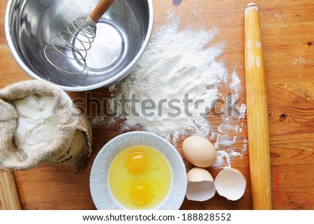 Kitchen rolling pin, eggs  and flour on wooden background - stock photo