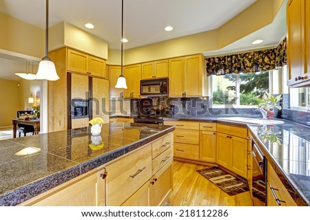 Kitchen room with backsplash trim, granite tops and black appliances - stock photo