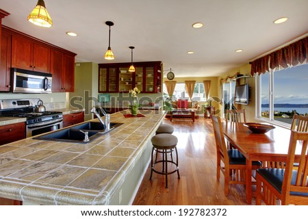 Kitchen room with dining area. View of kitchen island with built-in sink and dining table set - stock photo
