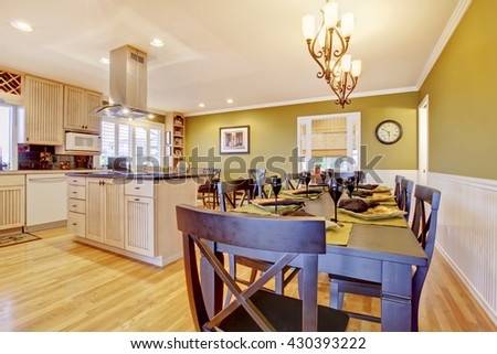 Kitchen room with green walls and wooden dining table - stock photo