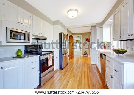 Kitchen room with hardwood floor, white storage combination and steel appliances - stock photo