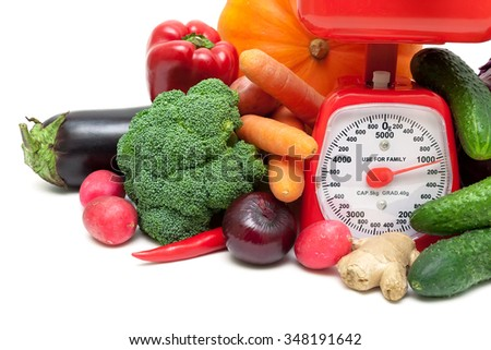 kitchen scale and vegetables on a white background. horizontal photo. - stock photo
