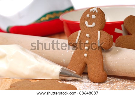 Kitchen scene showing the making and decorating of Christmas gingerbread men. - stock photo