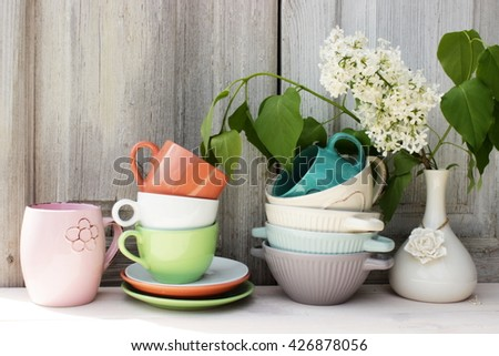 Kitchen shelf with vintage dishware in a cozy rustic setting. Retro style. Tender, pastel color - stock photo