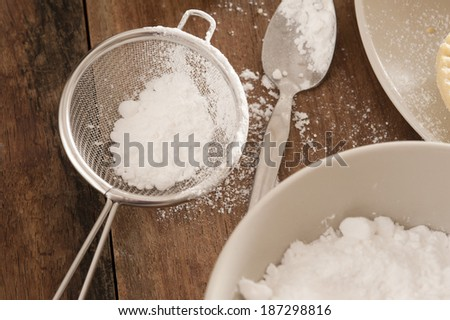 Kitchen sieve filled with icing sugar lying on a wooden kitchen counter alongside a mixing bowl while baking or cooking pastries and food - stock photo