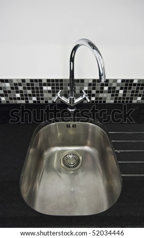 kitchen sink detail with a back granite worktop and designer water tap - stock photo