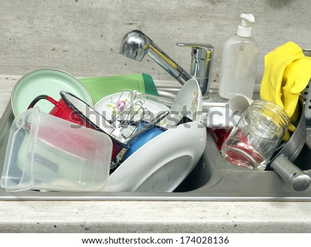 Kitchen sink full of dirty kitchenware - stock photo