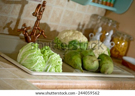 kitchen sink macro photo of vegetables in the foreground low deep of field - stock photo