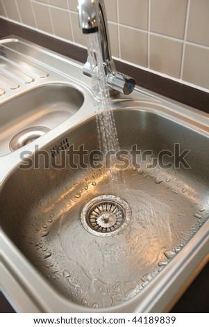 Kitchen sink with chrome mixer tap - stock photo