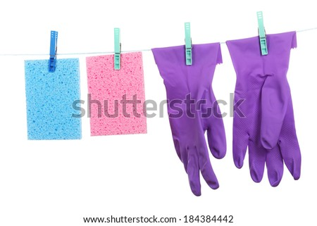 Kitchen sponges and rubber gloves hanging on rope isolated on white