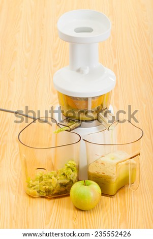 kitchen table, slow juicer making apple organic juice - stock photo
