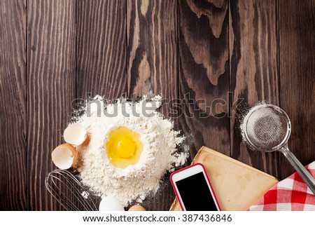 Kitchen table with ingredients, utensils and vintage recipe cooking book. Top view with copy space - stock photo