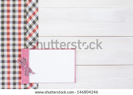 Kitchen tablecloth, recipe book on white wood - stock photo