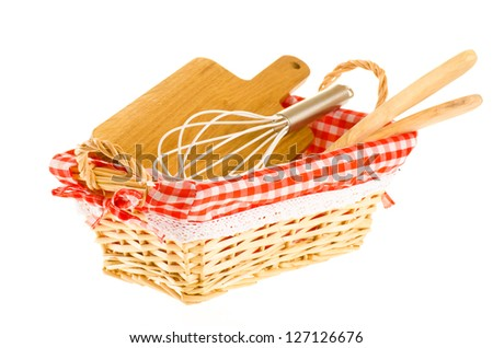 Kitchen tools in the basket, consisting of whisk, cutting board, and wooden spatulas - stock photo