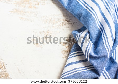 Kitchen towel or napkin  over the rustic wooden table. View from above with copy space