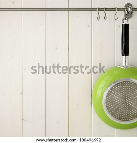 Kitchen utensil on steel rack against white wooden wall - stock photo