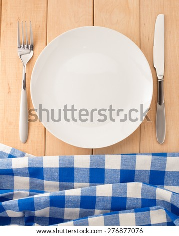 kitchen utensils and cloth napkin on wooden background - stock photo