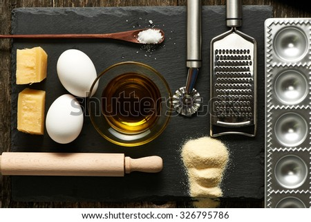 Kitchen utensils and ingredients for homemade pasta ravioli on slate - stock photo