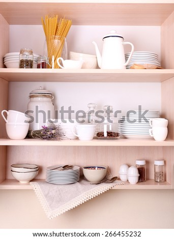 Kitchen utensils and tableware on wooden shelves - stock photo