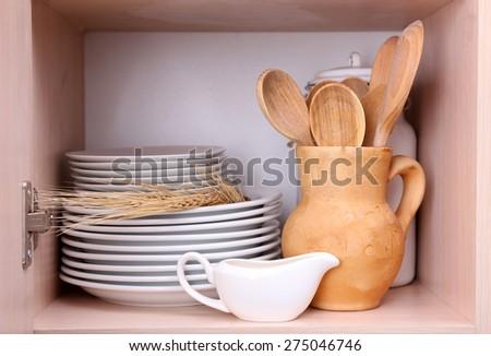 Kitchen utensils and tableware on wooden shelves - stock photo