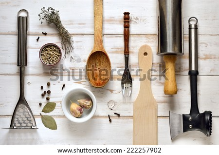 Kitchen utensils on a light rustic wooden background - stock photo
