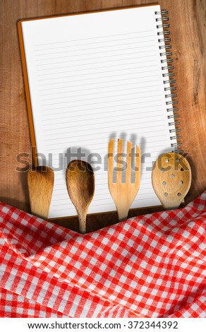 Kitchen Utensils on Wooden Table with Notebook / Open notebook for recipes or menu on an wooden table with checkered tablecloth and wooden kitchen utensils, fork, spoons and ladles - stock photo