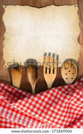 Kitchen Utensils on Wooden Table with Tablecloth / Wooden kitchen utensils, fork, spoons and ladles on a wooden table with checkered tablecloth and empty parchment for recipes of food menu - stock photo