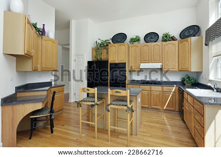 Kitchen with island and oak wood cabinetry - stock photo