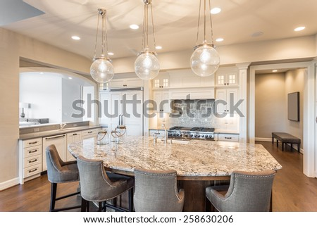 Kitchen with Island, Sink, Cabinets, and Hardwood Floors - stock photo