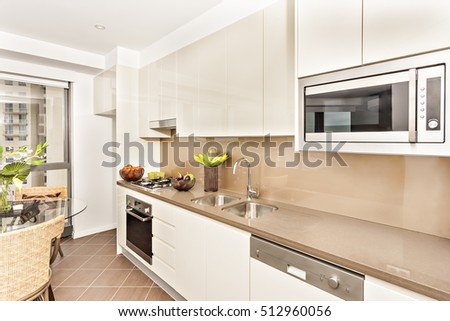 Kitchen with luxurious tools and white walls, luxury living room with chairs, oven and gas cooker have attached to the pantry cupboard, flower pot on the glass table, chairs are wooden in yellow.