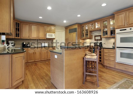 Kitchen with oak cabinetry and double decker island - stock photo