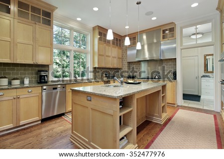 Kitchen with oak wood cabinetry and granite counter - stock photo