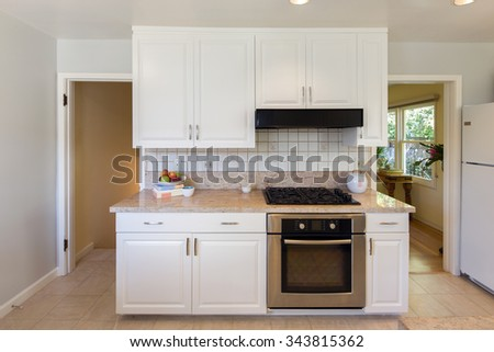 Kitchen with table and chairs, with wooden cabinetry and built in appliances and oven. - stock photo
