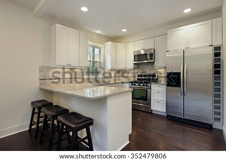 Kitchen with white cabinetry and breakfast bar - stock photo
