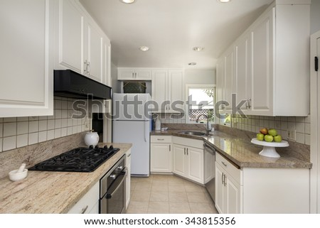 Kitchen with white cabinetry and built in appliances on a white floor. - stock photo