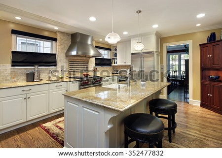 Kitchen with white cabinetry and center island - stock photo