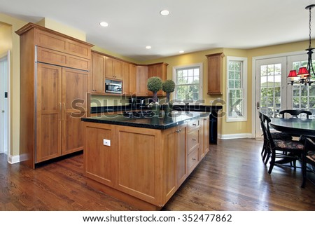 Kitchen with wood cabinetry and granite counter - stock photo