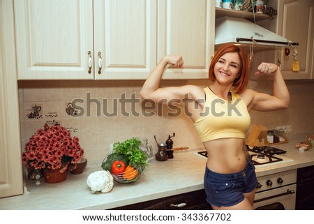 kitchen woman making healthy food standing happy smiling in kitchen preparing salad. Beautiful cheerful Caucasian young sport woman at home. - stock photo