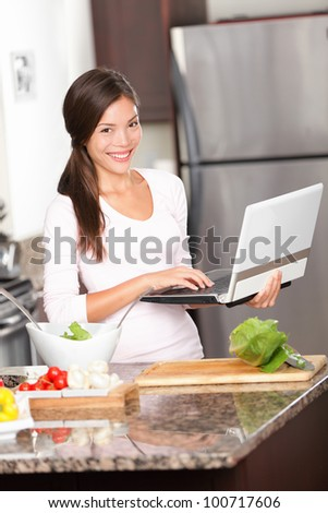 Kitchen woman on laptop PC cooking making food using computer for recipes etc. Beautiful young modern lifestyle image of multiracial Caucasian / Chinese asian young woman at home. - stock photo