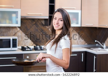 Kitchen Woman. Young beautiful girl holding a frying pan. Cooking. Kitchen background - stock photo
