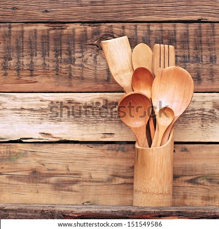 Kitchen wooden utensils in retro bucket over wooden background - stock photo