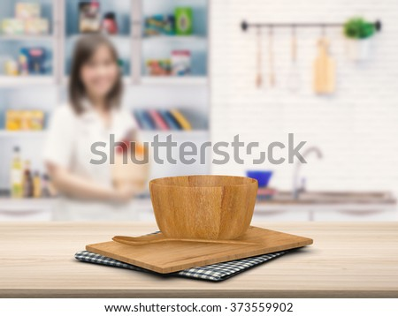 kitchenware on wooden counter with kitchen blurred background - stock photo