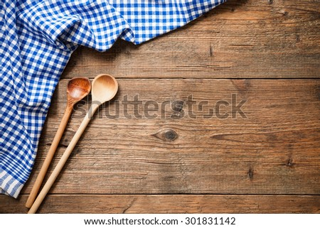 Kitchenware on wooden table with a blue checkered tablecloth - stock photo
