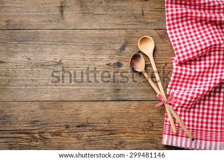 Kitchenware on wooden table with a red checkered tablecloth - stock photo