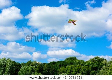 Kite flying against a blue background with clouds over the trees are not - stock photo