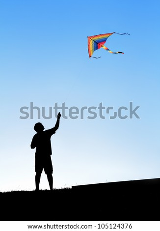 Kite in the sky. Silhouette of a man. - stock photo