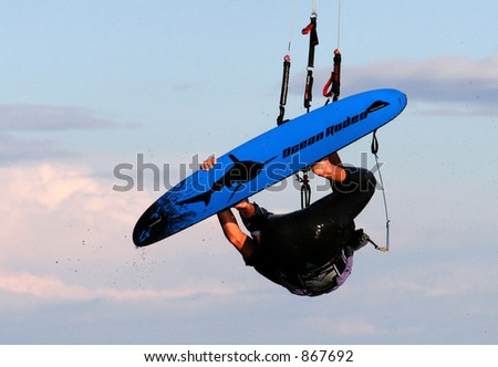 Kite surfer jumping into the air on a gust of wind - stock photo