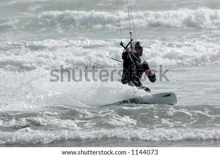 Kite surfer ( kite boarder ) riding the waves  near Cayucos, California. - stock photo