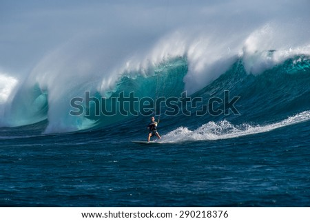 Kite surfer rides among the huge tubes and waves of the Indian Ocean on the island of Mauritius - stock photo